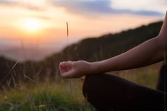Woman doing yoga meditation in the mountains at dawn Stock Image