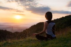 Woman doing yoga meditation in the mountains at dawn Stock Photo