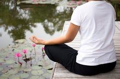 Woman doing yoga meditation next to lotus pond Stock Image