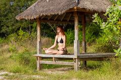 Woman doing yoga meditation in tropical gazebo Stock Photo