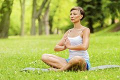 Woman doing yoga on the medow. Royalty Free Stock Image