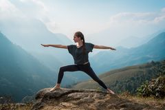 Woman doing yoga on mountain cliff at sunrise. Mountanious landscape