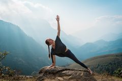 Woman doing yoga on mountain cliff at sunrise. Mountanious landscape