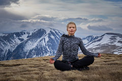 Woman doing yoga on mountain Royalty Free Stock Images