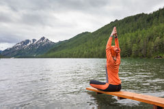 Woman is doing yoga at Multinskoe lake Royalty Free Stock Photo