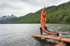 Woman is doing yoga at Multinskoe lake Stock Photos