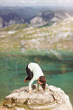 Woman doing yoga in nature. Woman doing yoga on a rock on the lake shore Royalty Free Stock Images