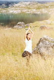 Woman doing yoga in nature. Young woman doing yoga exercises in high grass Royalty Free Stock Images