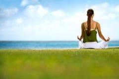 Woman doing yoga near the ocean Stock Photo
