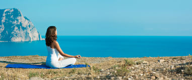 Woman Doing Yoga near the Ocean royalty free stock photography