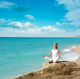 Woman Doing Yoga near the Sea stock photography