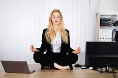 Woman Doing Yoga In Office. A Young Woman Doing Yoga While Sitting On Wooden Desk royalty free stock photos