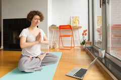 Woman doing yoga with online app on computer in her living room. Healthy lifestyle and work life balance concepts. Horizontal, natural light Royalty Free Stock Photos