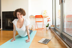 Woman doing yoga with online app on computer in her living room. Healthy lifestyle and work life balance concepts. Horizontal, natural light Royalty Free Stock Images