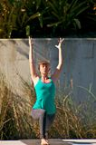 Woman doing yoga outdoors in warrior one pose Royalty Free Stock Photos