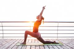 Woman doing yoga outdoors in the morning royalty free stock images