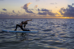 Woman doing yoga on a paddle board Royalty Free Stock Photos