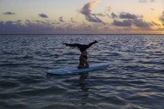 Woman doing yoga on a paddle board Royalty Free Stock Photography