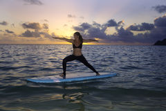 Woman doing yoga on a paddle board Stock Photography