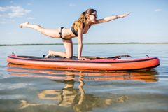 Woman doing yoga on the paddleboard. Young woman doing yoga on the paddleboard on the lake with calm water and reflection during the morning light stock photo