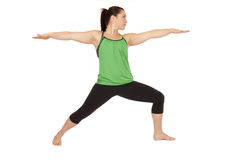 Woman doing yoga pose called warrior 2 arms out Stock Photography
