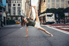 Woman doing yoga pose in the city street of New York. Woman doing yoga pose in the city street of New York royalty free stock image