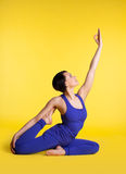 Woman doing yoga pose - sit in blue on yellow Royalty Free Stock Photo