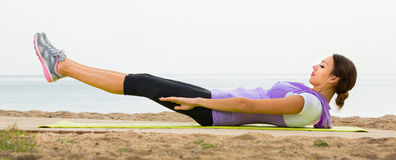 Woman doing yoga poses sitting on sunny beach Stock Photography