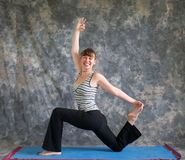 Woman doing Yoga posture King Arthurs pose Royalty Free Stock Photos