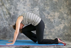 Woman doing Yoga posture strong cat po. Young woman on yoga mat in  Yoga posture Marjaryasana variation or strong cat pose with right knee to forehead, against a Royalty Free Stock Image