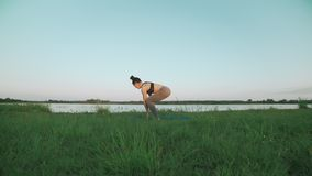 Woman doing yoga in quiet scenery. Yoga, sport and healthy lifestyle concept. Woman doing yoga in quiet scenery. Beautiful young girl wearing sports clothes stock footage
