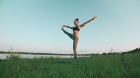Woman doing yoga in quiet scenery. Yoga, sport and healthy lifestyle concept. Woman doing yoga in quiet scenery. Beautiful young girl wearing sports clothes stock video footage
