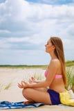 Woman doing yoga on sandy beach. Royalty Free Stock Image