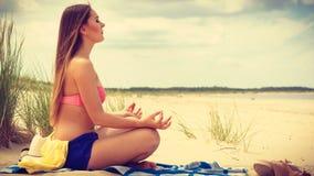 Woman doing yoga on sandy beach. Stock Images