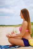 Woman doing yoga on sandy beach. Royalty Free Stock Photos
