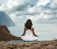 Woman Doing Yoga at the Sea and Mountains Royalty Free Stock Photos
