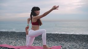 Woman doing yoga on a shore in the morning. stock video