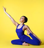 Woman doing yoga split in blue on yellow Royalty Free Stock Images
