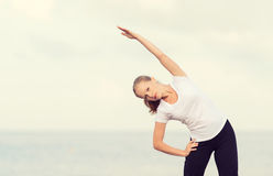 Woman doing yoga and sport exercises on  beach Royalty Free Stock Image
