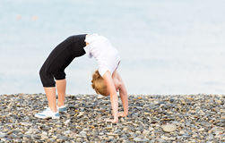 Woman doing yoga and sport exercises on  beach Stock Photos