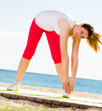 Woman doing yoga standing Stock Images