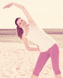 Woman doing yoga standing. Smiling girl practicing yoga poses standing on beach by sea at daylight Stock Photography