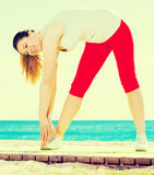 Woman doing yoga standing. Smiling girl practicing yoga poses standing on beach by sea at daylight Stock Image