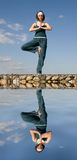 A woman doing yoga on a stone above  water Royalty Free Stock Photo