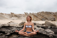 Woman doing yoga on the stone nearby sea Royalty Free Stock Photo