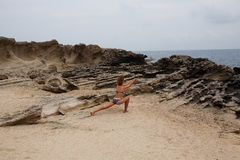 Woman doing yoga on the stone nearby sea Stock Photography