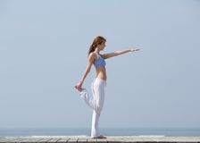Woman doing yoga stretches at the beach Stock Photos