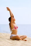 Woman doing yoga by stretching her arms. Woman stretching arms at the beach relaxing doing yoga Stock Image