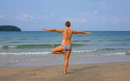 Woman doing yoga on sunny beach. Tropical seaside vacation activity. Young girl in asana posture. Meditation on seashore. White sand beach view with woman in Stock Photo