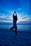 Woman doing yoga at the sunset beach Royalty Free Stock Image